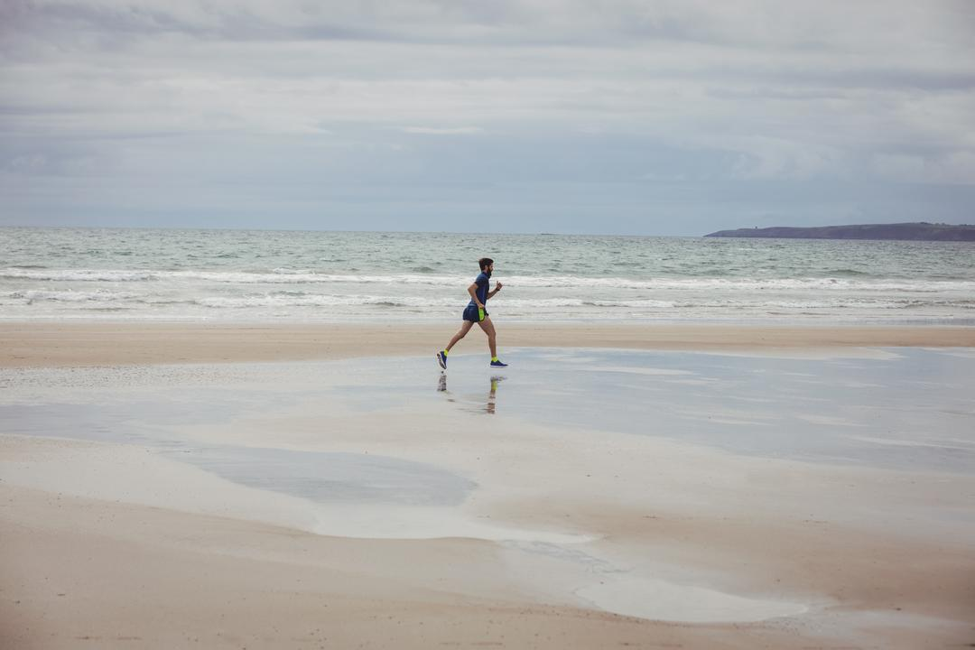 Athlete running along the beach on a sunny day