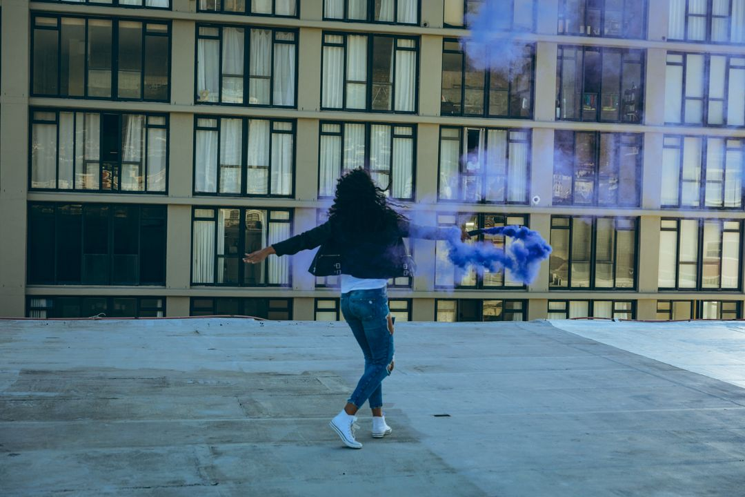 Rear view of a hip young mixed race woman wearing leather jacket and jeans, holding a smoke grenade with purple smoke on an urban rooftop with building in the background Free Stock Images from PikWizard