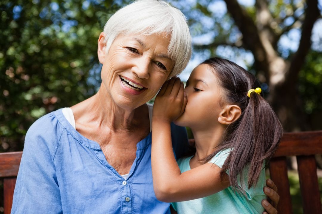 Girl whispering in ears of smiling grandmother at backyard Free Stock Images from PikWizard