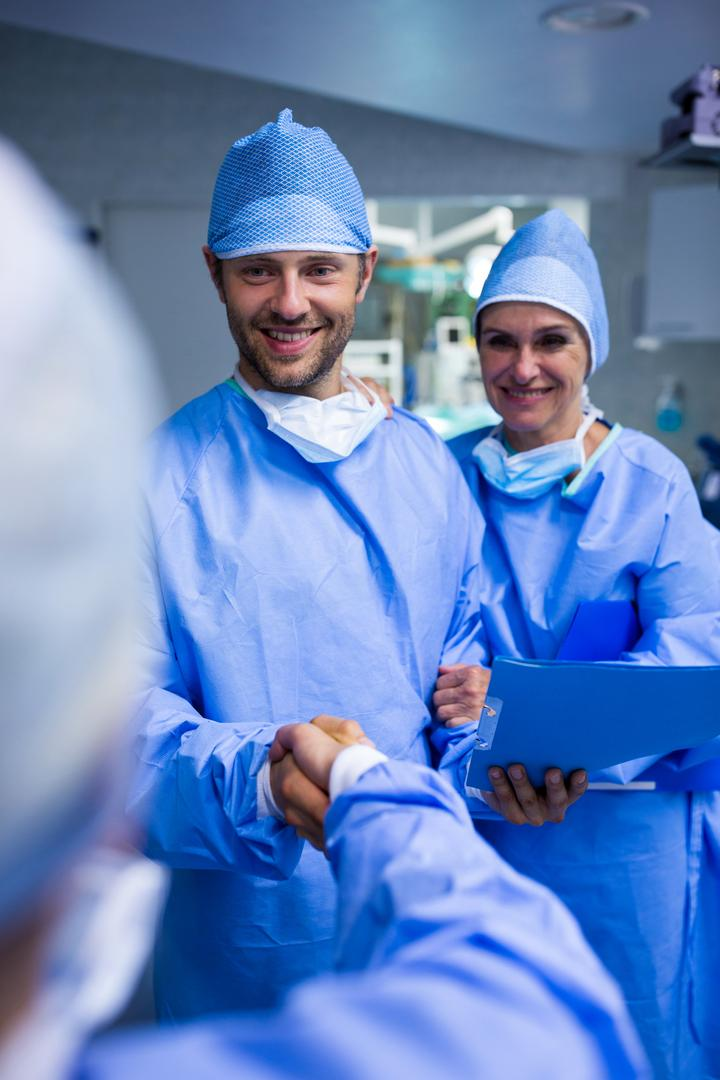 Surgeons shaking hand in operation room at hospital