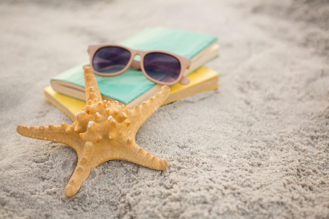Starfish, sunglasses and books on sand at beach Free Stock Images from PikWizard