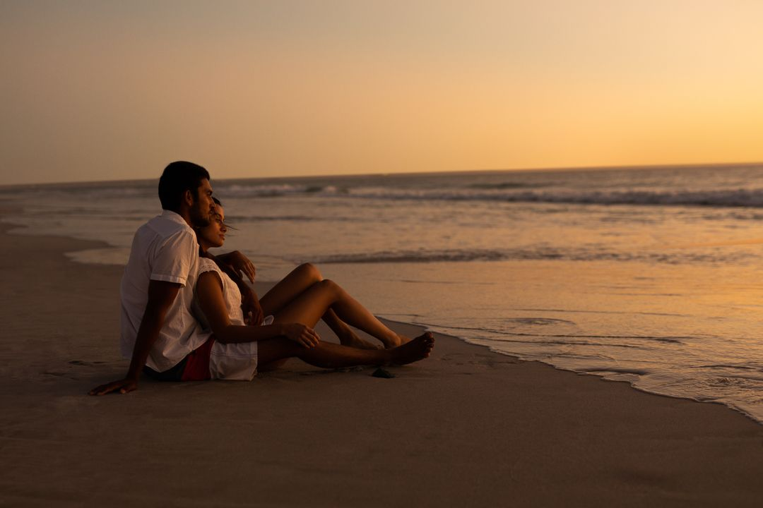 Young couple looking at sea on the beach during sunset