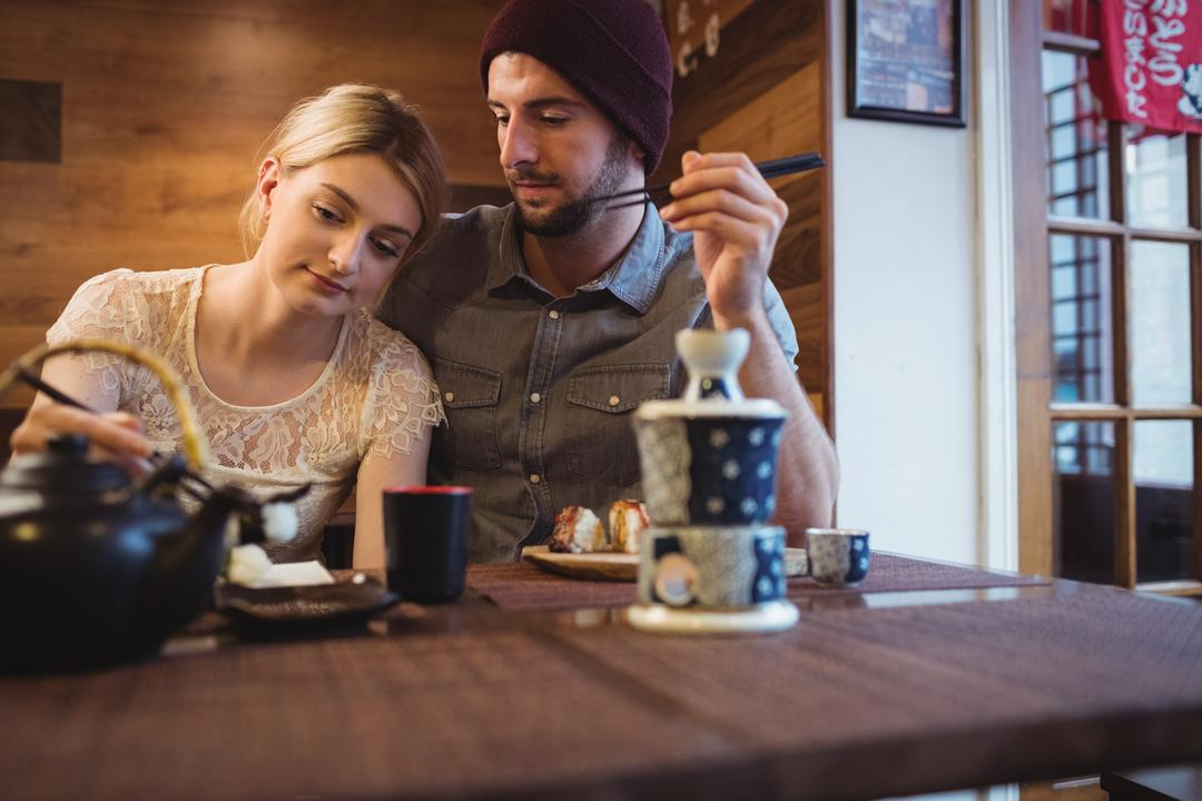 Couple romancing while having sushi in restaurant