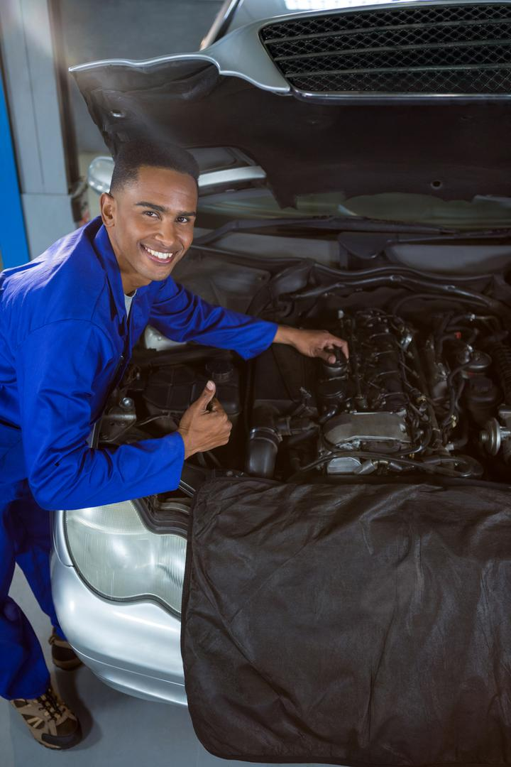 Portrait of happy mechanic showing thumbs up while repairing car at garage