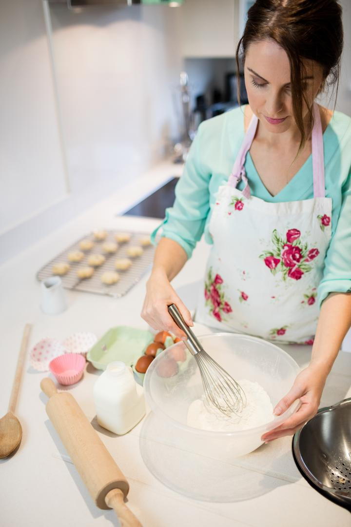 Beautiful woman whisking flour in bowl at kitchen
