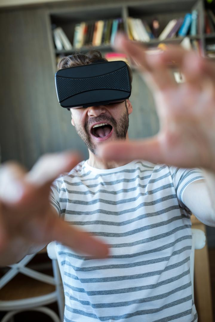 Excited man using virtual reality headset in coffee shop Free Stock Images from PikWizard