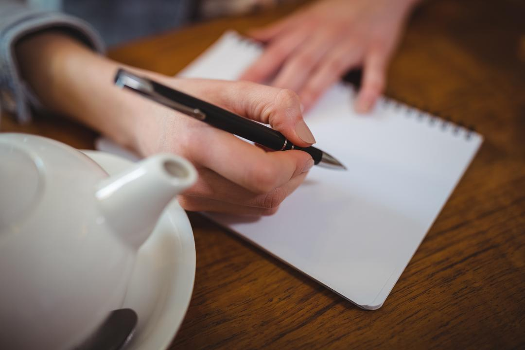 Woman sitting at table and writing on notepad in café Free Stock Images from PikWizard