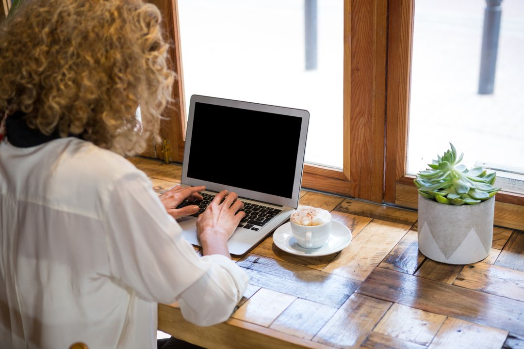 Rear view of young woman using laptop in coffee shop Free Stock Images from PikWizard