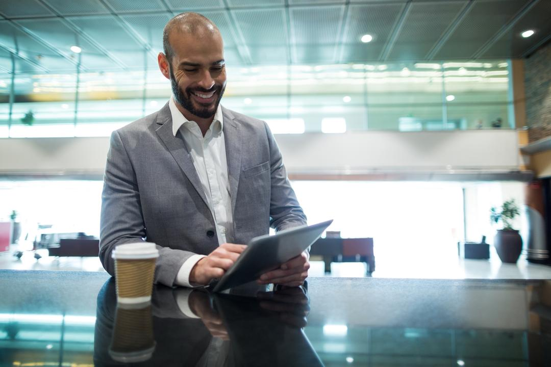 Smiling businessman using digital tablet in waiting area at airport terminal