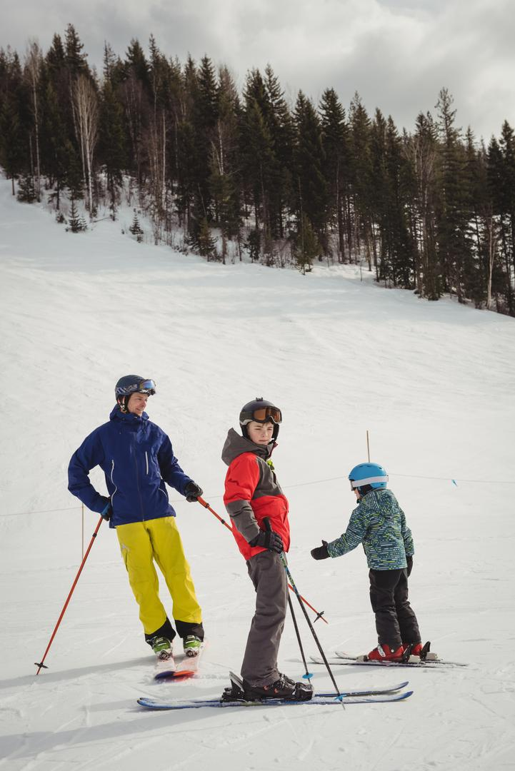 Father and kids skiing on snowy alps during winter