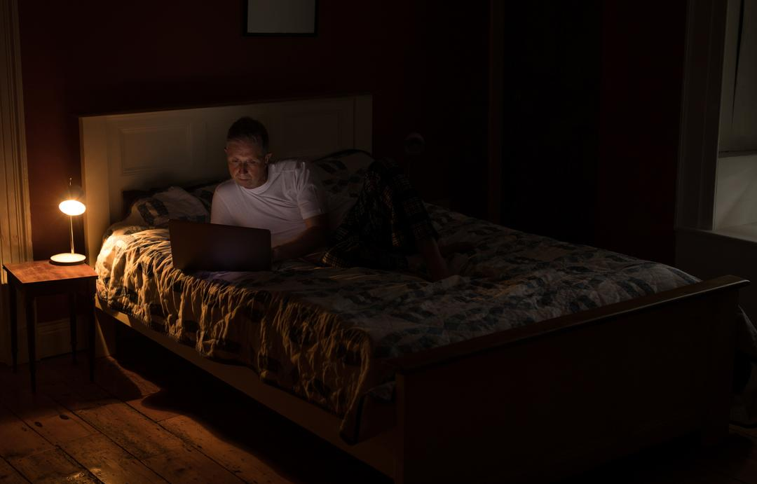 Senior man using laptop in bedroom at home