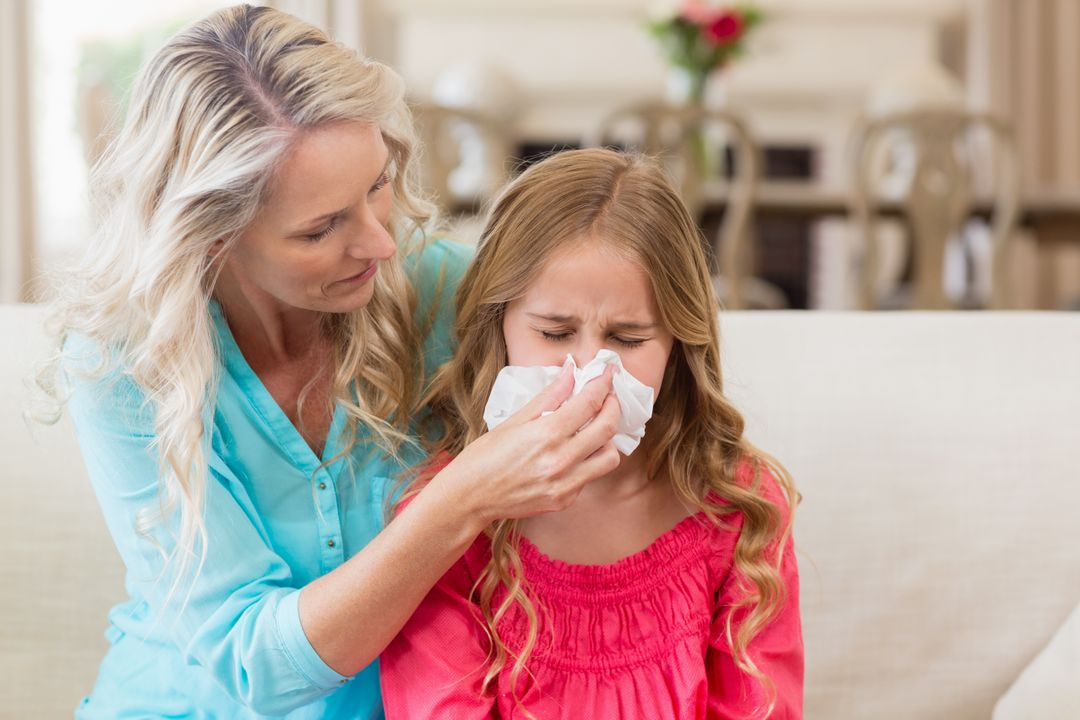 Mother helping daughter blowing her nose on sofa in living room at home