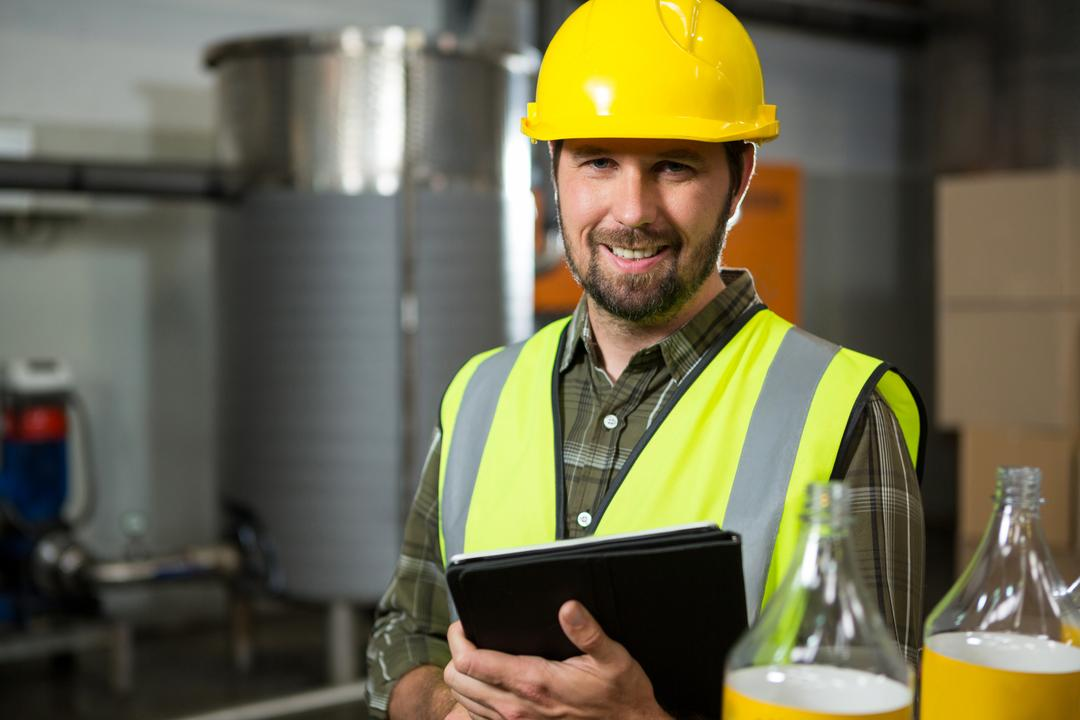 Portrait of smiling male worker holding digital tablet in factory
