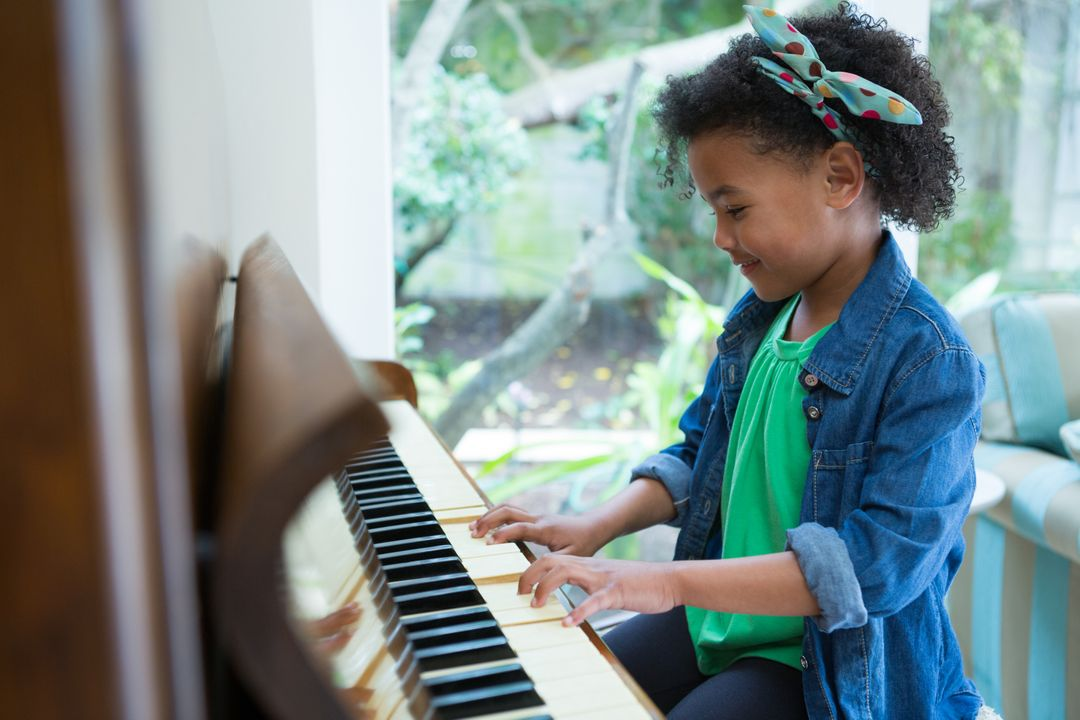Adorable girl playing piano at home Free Stock Images from PikWizard