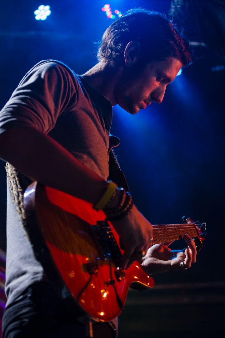 Guitarist playing guitar on stage in nightclub Free Stock Images from PikWizard