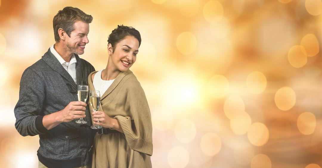 Digital composite of Happy couple holding champagne flutes over blur background