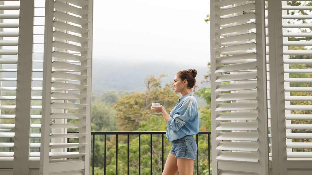 Beautiful woman standing in balcony while having coffee in a comfortable home