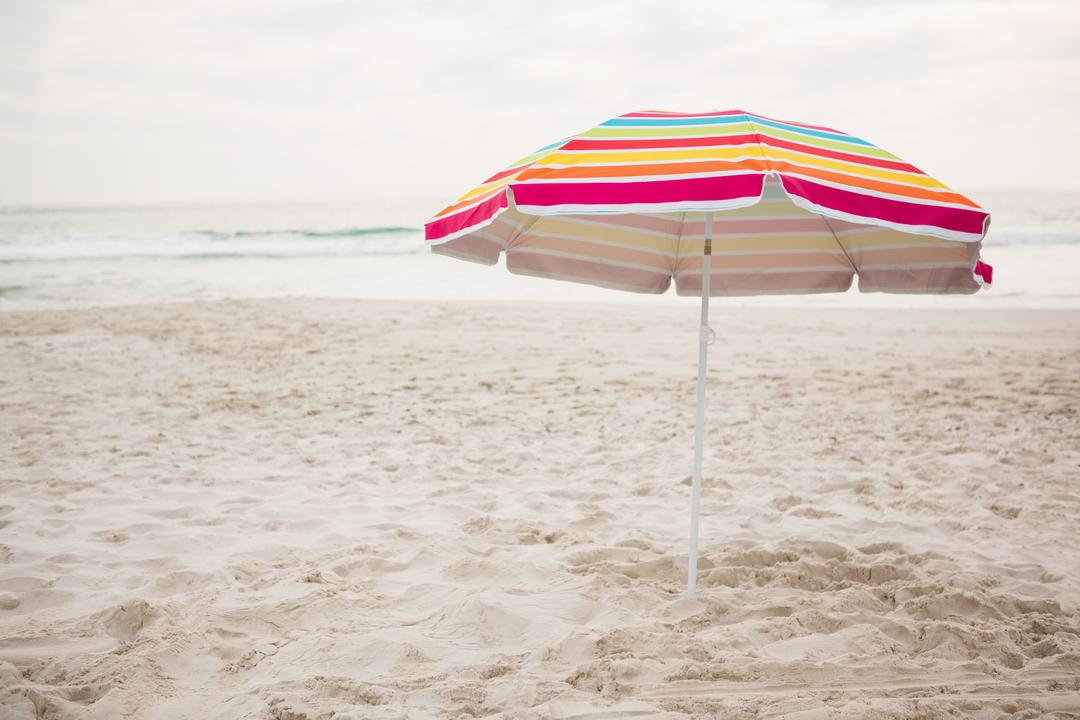 Multi-color striped beach umbrella at tropical sand beach