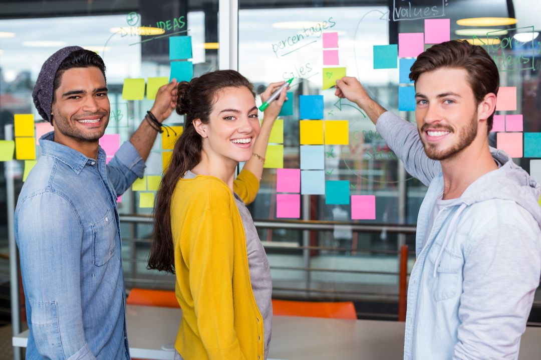 Portrait of smiling executives writing on sticky note on glass wall in office