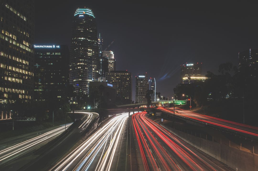 Slow motion image of car lights on a busy highway with an in focus view of the city background
