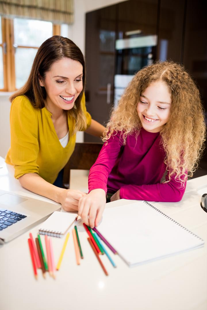 Mother and daughter helping daughter with her homework in kitchen