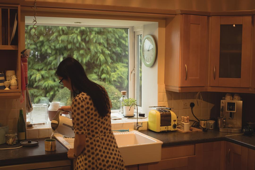 Woman preparing coffee in kitchen at home