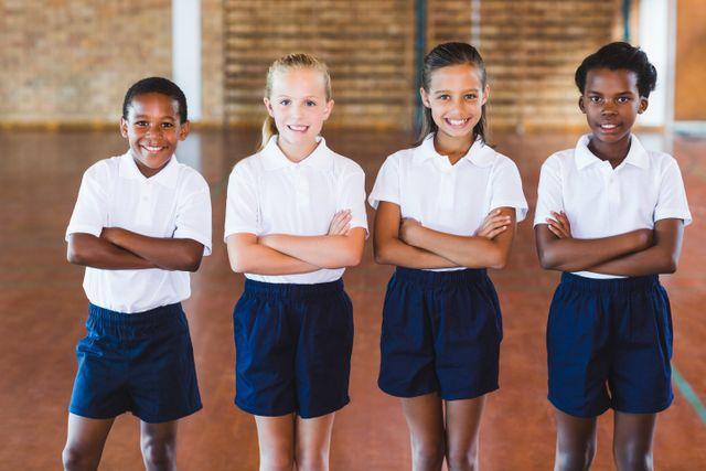 Portrait of school kids standing with arms crossed in basketball court at school gym