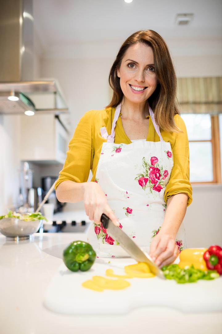 Portrait of beautiful woman cutting vegetables on chopping board in kitchen