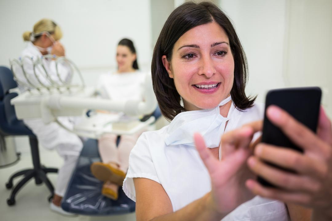 Female doctor using mobile phone at clinic