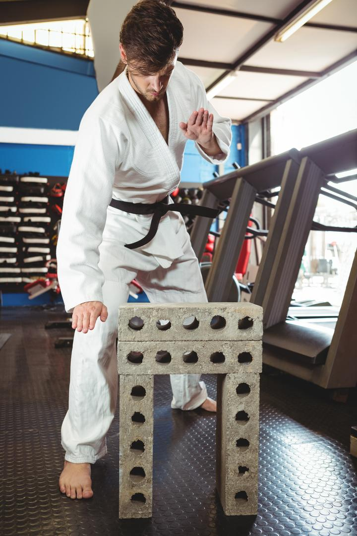 Karate player breaking concrete block in fitness studio