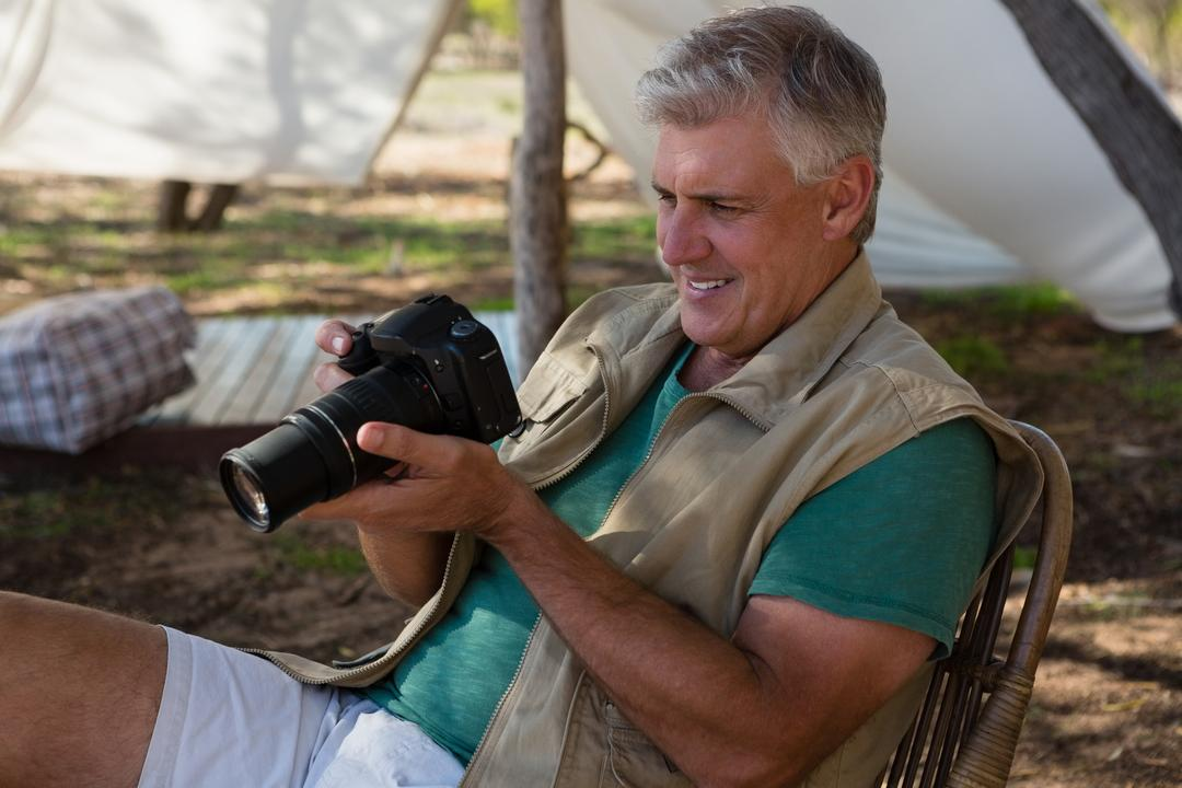 Man looking into camera outside tent