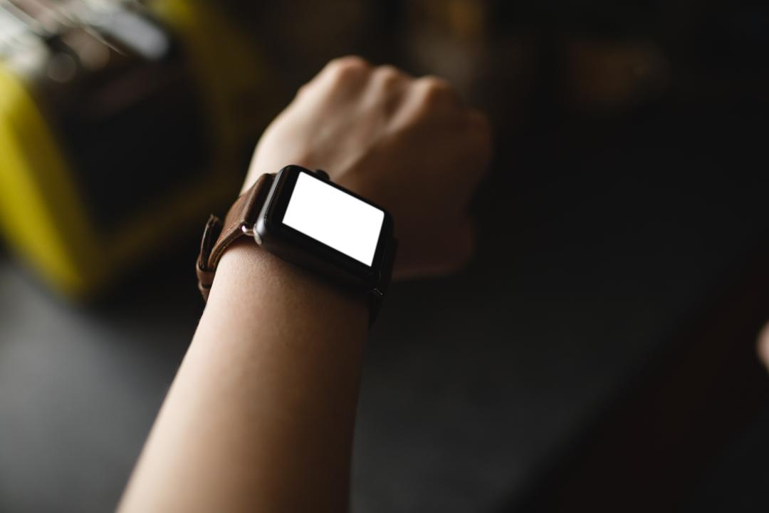 Close-up of woman wearing a smartwatch at home
