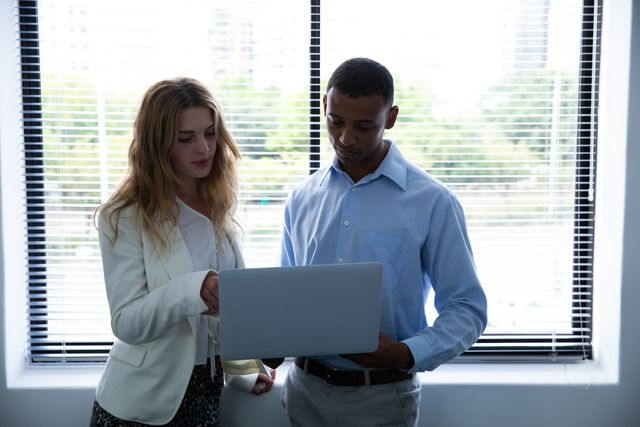 Front view of a young African American man and a young Caucasian woman standing behind a window looking at a tablet computer together in the office of a creative business.