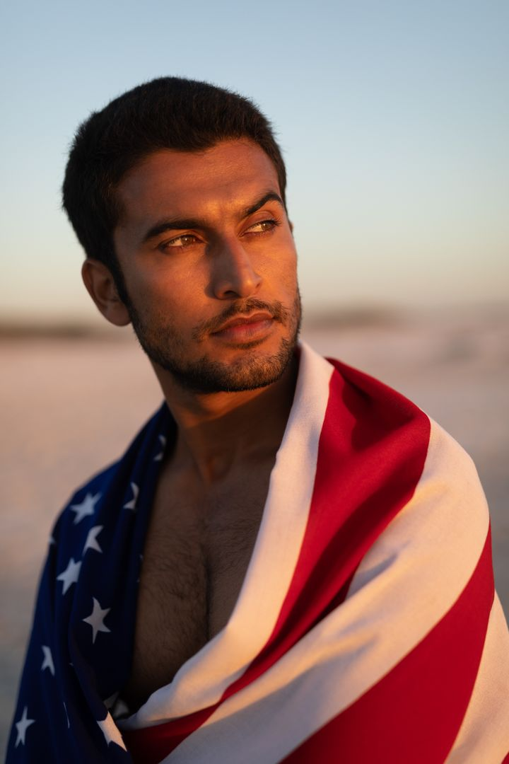 Young man wrapped in American flag standing on the beach