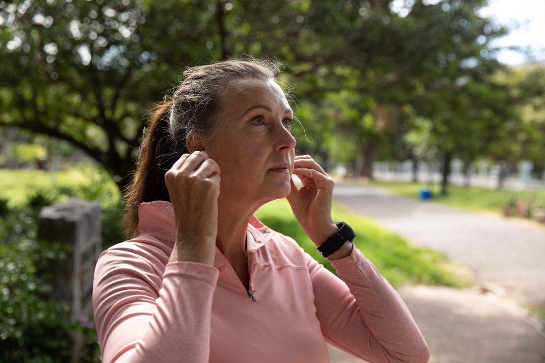 Senior Caucasian woman working out in the park wearing sports clothes, putting earphones on. Retirement healthy lifestyle activity. Free Stock Images from PikWizard