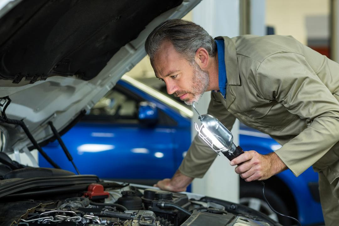 Mechanic examining a car with lamp in repair garage