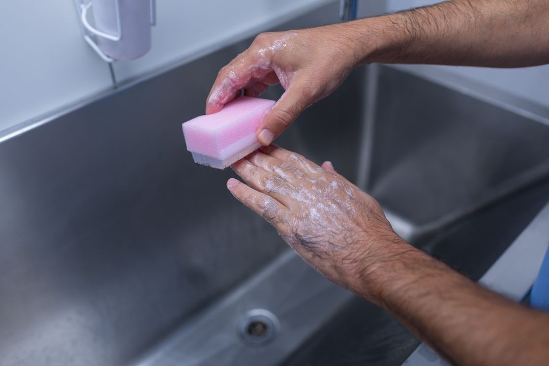 Close-up of male surgeon scrubbing hands with brush at sink in hospital