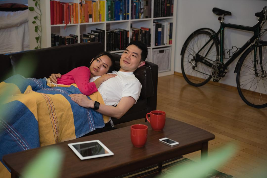 Affectionate couple relaxing on sofa in living room at home