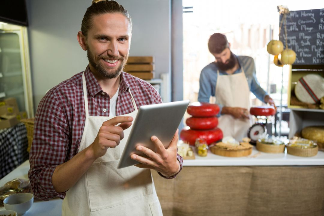 Portrait of smiling staff using digital tablet in market Free Stock Images from PikWizard