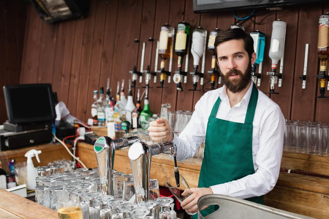 Portrait of bartender filling beer from bar pump at bar counter