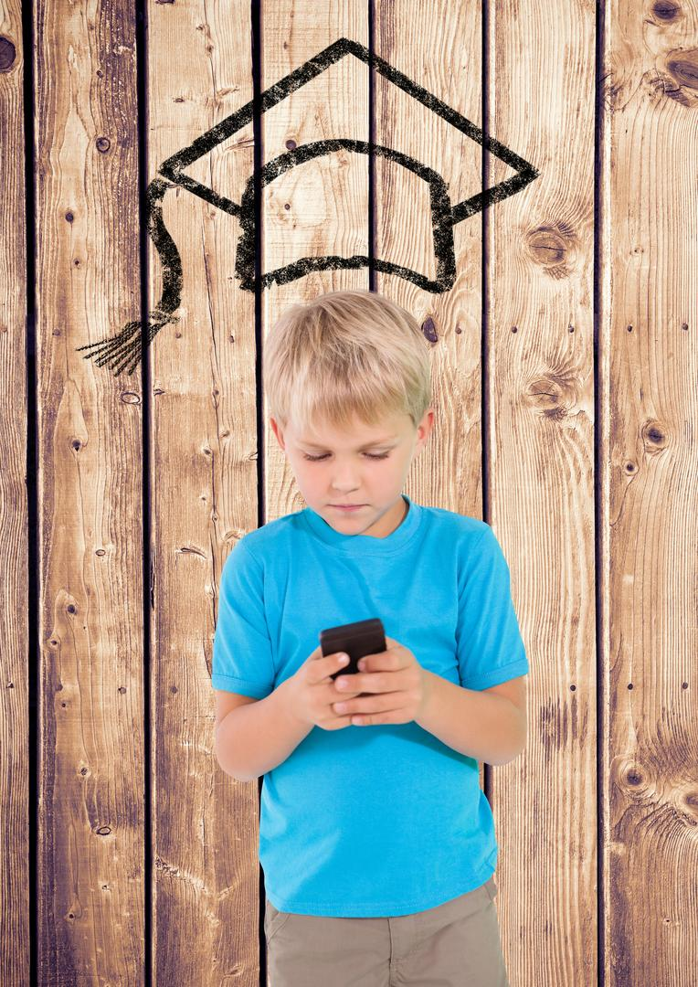 Digital composition of boy using mobile phone with graduation hat on wooden background