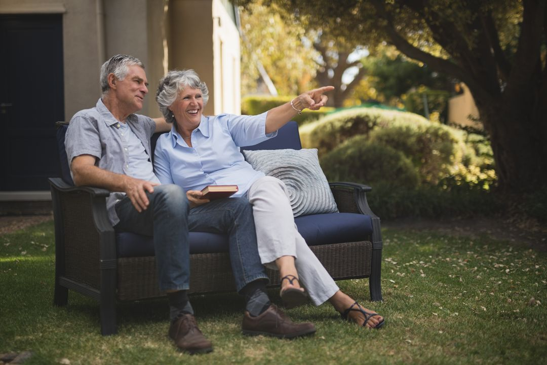 Happy senior couple sitting together on couch in backyard Free Stock Images from PikWizard