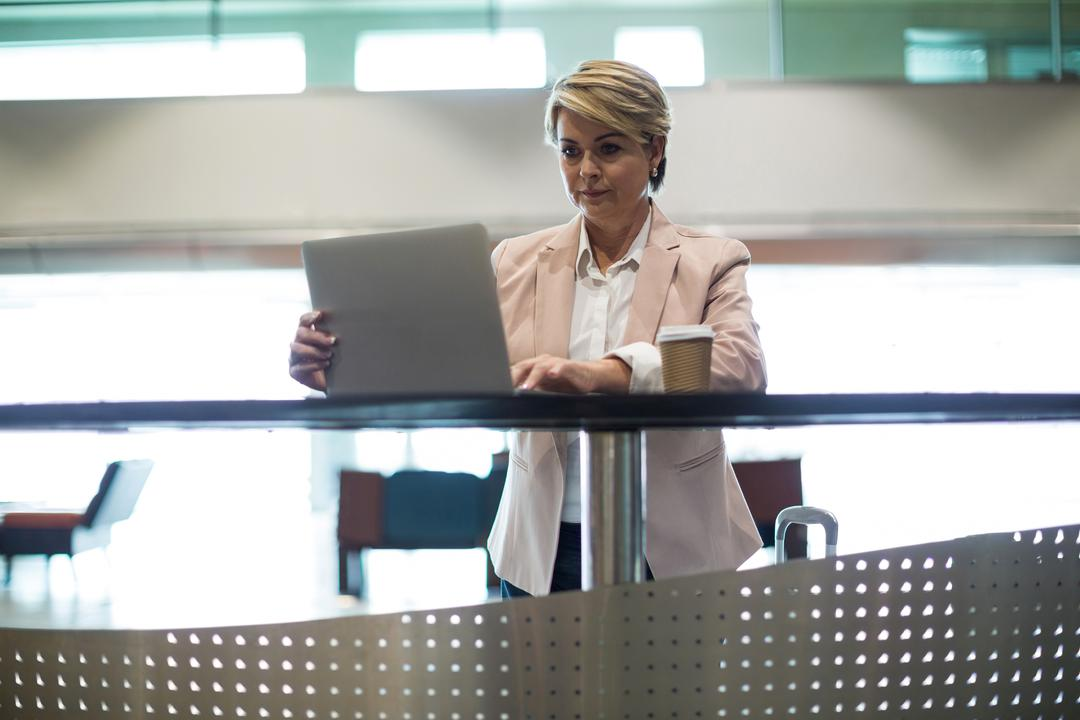 Businesswoman using laptop in waiting area at airport terminal