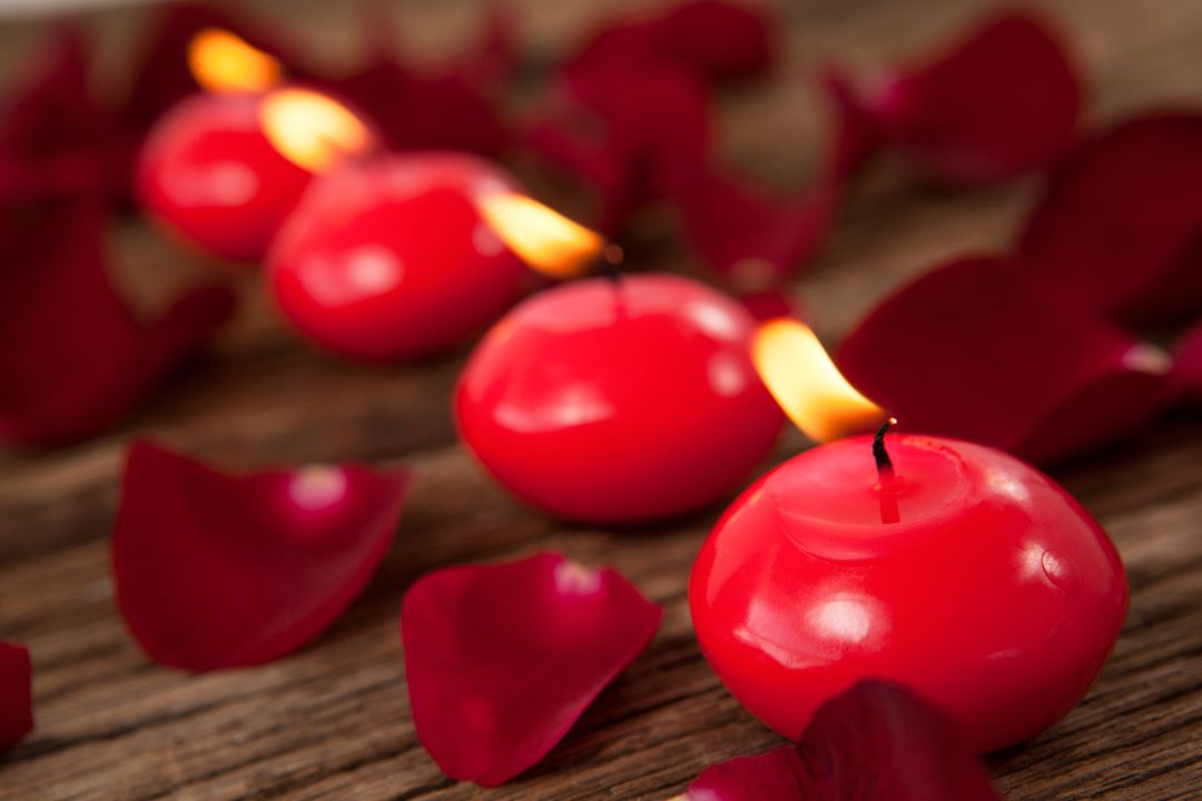 Red wax candles surrounded with rose petals against wooden background