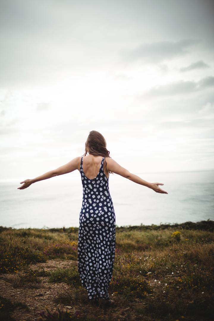 Rear view woman standing with arms outstretched on cliff over sea