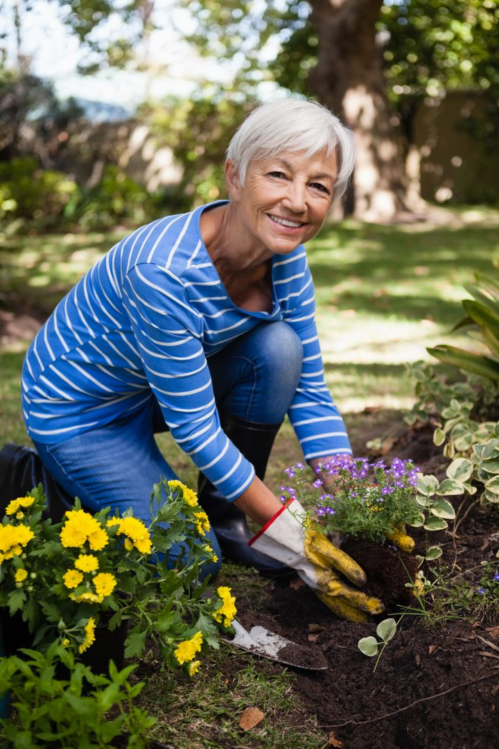 Portrait of smiling senior woman planting flowers in backyard Free Stock Images from PikWizard