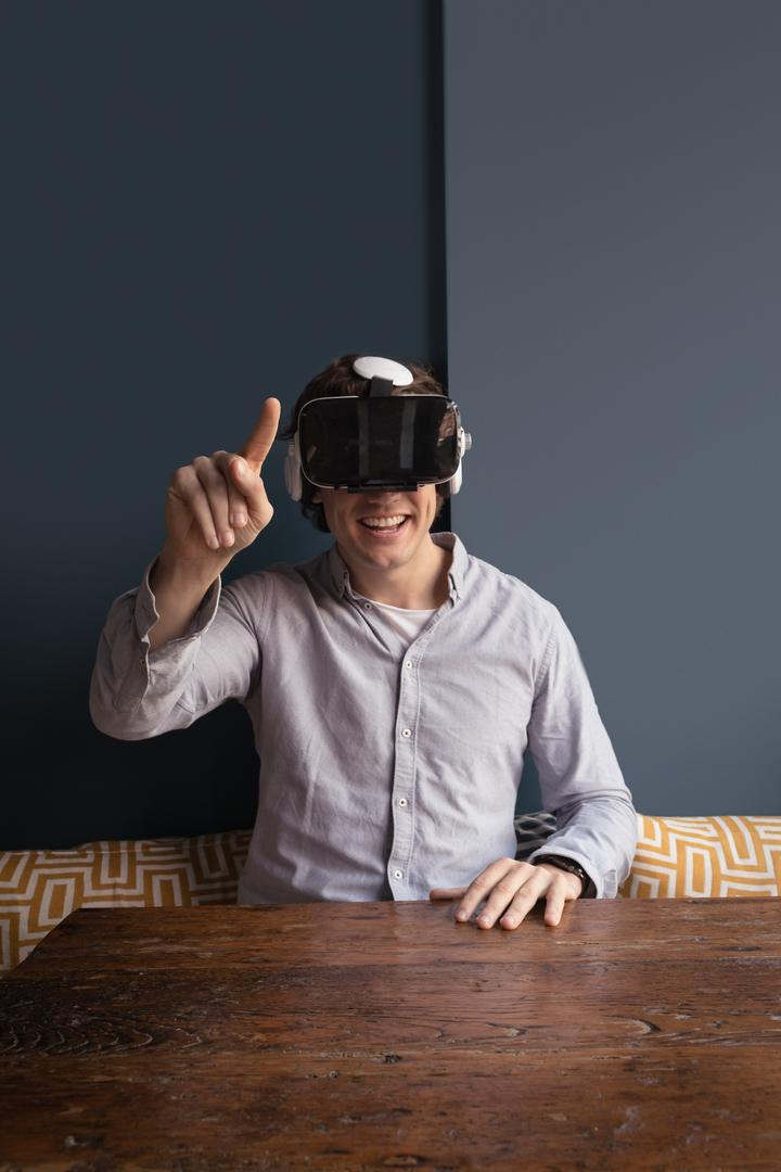 Happy man using virtual reality headset in café