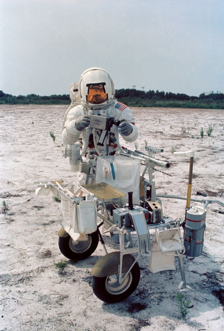 "S70-46191 (July 1970) --- Astronaut Alan B. Shepard Jr., commander of the Apollo 14 lunar landing mission, participates in lunar surface training at the Kennedy Space Center (KSC). Shepard is adjusting a camera mounted to the modular equipment transporter (MET). The MET, nicknamed the ""Rickshaw"", will serve as a portable work bench with a place for the Apollo lunar hand tools and their carrier, three cameras, two sample container bags, a special environment sample container, spare magazines, and a lunar surface Penetrometer. Shepard is wearing an Extravehicular Mobility Unit (EMU)."