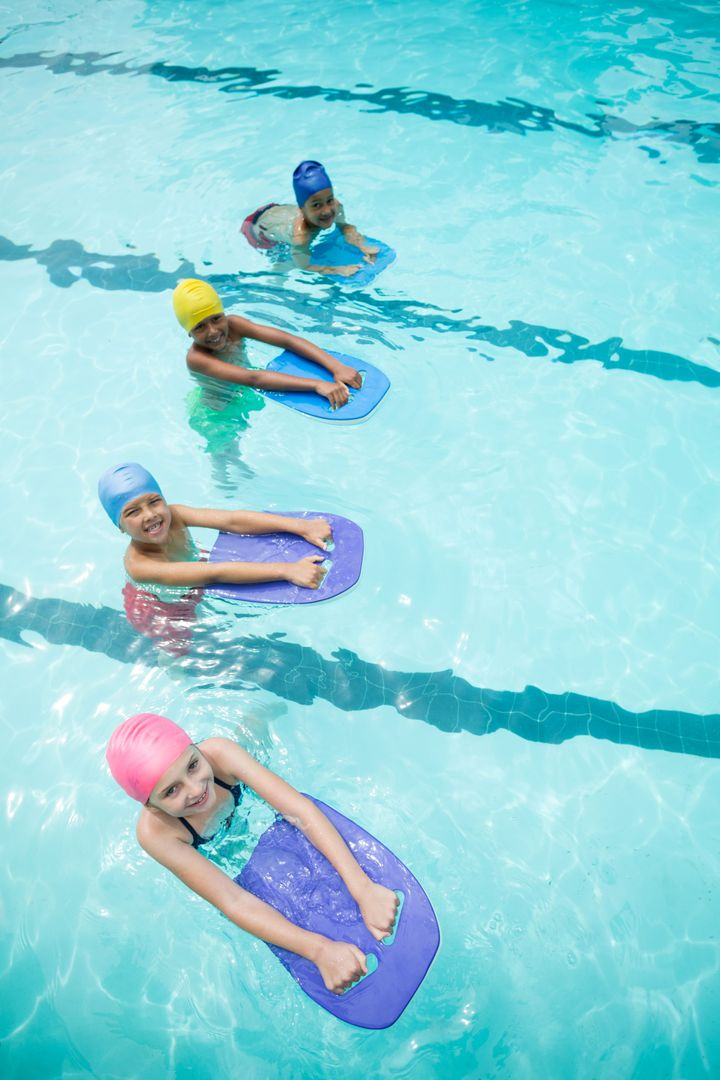 High angle view of children using kickboard while swimming in pool