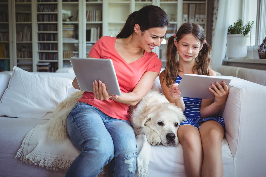 Mother and daughter sitting with pet dog and using digital tablet at home Free Stock Images from PikWizard